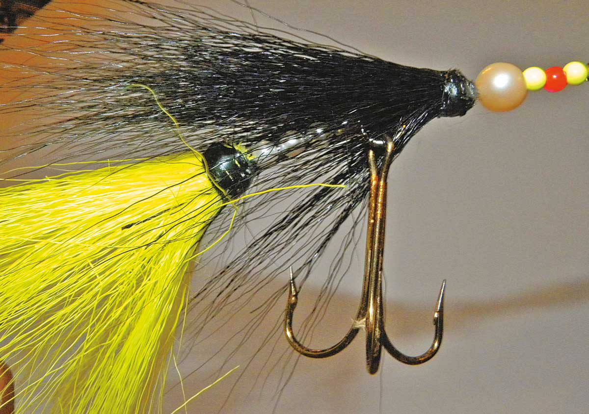 Hinter den Drilling ein Gewicht als Abstandhalter, dann den gelben Bucktail auffädeln.